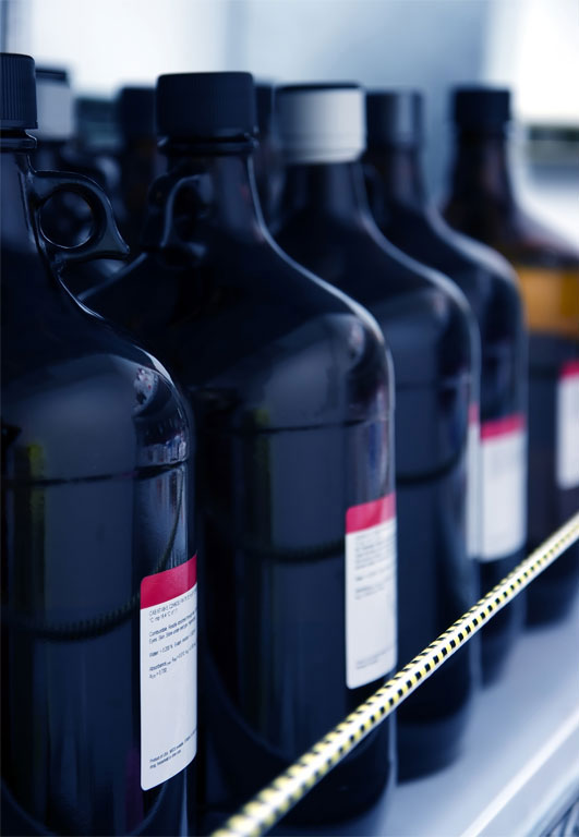 Flammable laboratory solvent bottles in a row