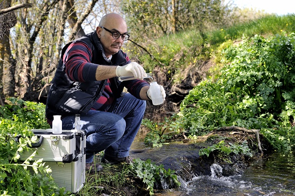 Collecting river water sample for environmental pollution testing