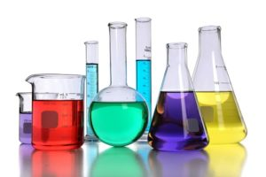 Laboratory glassware with various colored liquids with reflectio